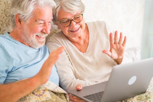Stary starszy para kaukaski uśmiechający się i wideo na czacie za pomocą laptopa rano w łóżku w sypialni w domu. starsi pozdrowienie na rozmowy wideo na laptopie w domu.