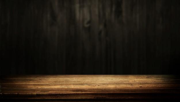 Stary stół z drewna z ciemno brązowe ściany rozmyte tło.