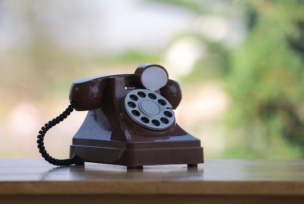 Stary styl retro telefonu palcowego na drewnianym stole barowym z zielonym tłem bokeh natury