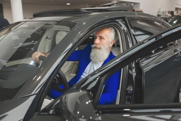 Stary stylowy mężczyzna w luksusowym samochodzie. mężczyzna z brodą i wąsem jazdy samochodem. salon sprzedaży samochodów.