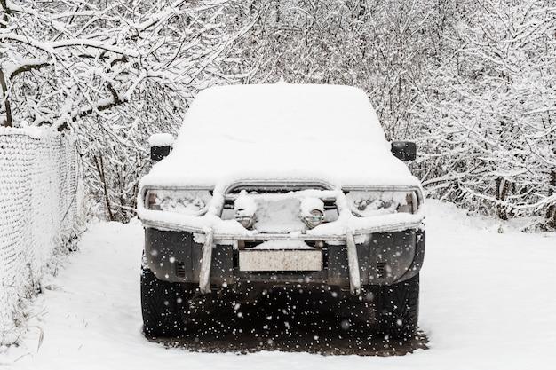 Stary suv pokryty pierwszym śniegiem.