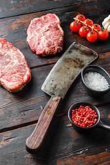 Stary tasak z nożem rzeźniczym w pobliżu górnego ostrza, kawałek mięsa organicznego, surowy marmurkowy stek wołowy i przyprawy na ciemnym drewnianym stole rustykalnym, widok z góry.