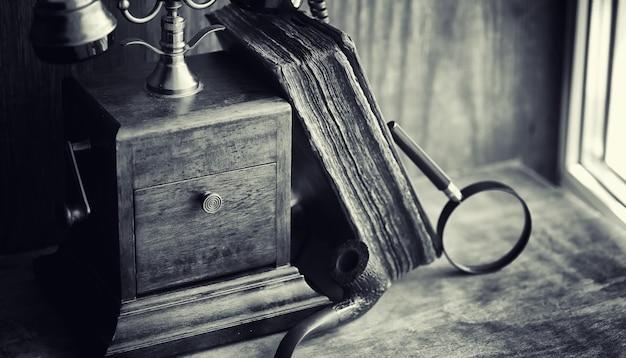 Stary telefon i retro książka na biurku. telefon z przeszłości na starym drewnianym blacie. rozmowy telefoniczne z xix wieku.