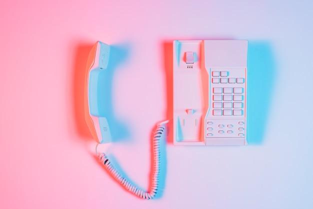 Stary telefon stacjonarny z odbiornikiem z niebieskim światłem cień na różowym tle