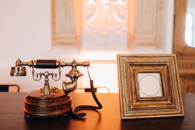 Stary telefon w stylu retro stoi obok pustej ramki na zdjęcia. vintage telefon i ramka na zdjęcia.