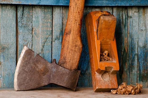 Stary topór, strugarki i wiórów na niebieskim drewnianym stole