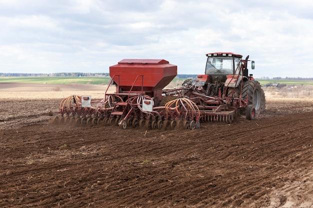 Stary traktor plonujący pszenicę w sezonie wiosennym.