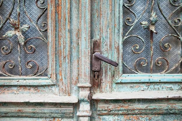 Stary uchwyt drzwi z bliska. metalowy uchwyt i zamek do starych drzwi drewnianych. vintage zielone drewniane drzwi z metalową kratą.