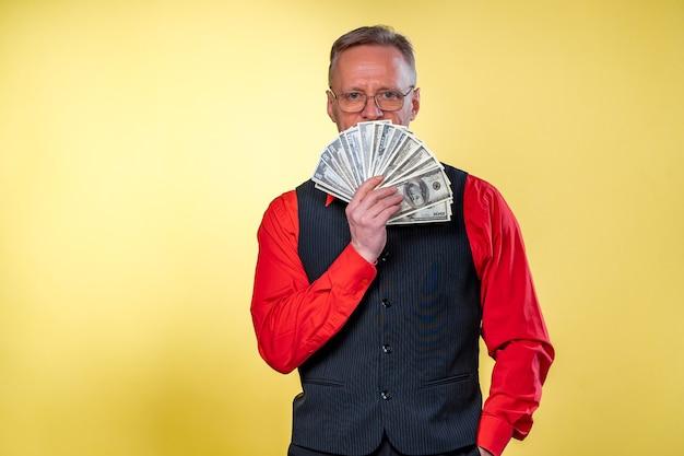 Stary uśmiechnięty siwy mężczyzna w okularach. człowiek posiadający wentylator dolarów w pobliżu twarzy. ludzkie emocje i mimika twarzy