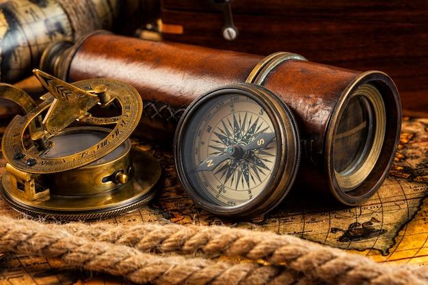 Stary vintage kompas i instrumenty nawigacyjne na starożytnej mapie
