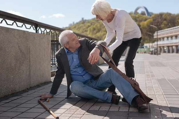 Stary wesoły, uroczy mężczyzna potyka się i klapsa, podczas gdy delikatna kobieta podnosi tego mężczyznę