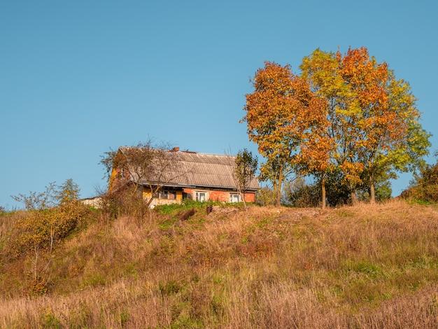 Stary wiejski dom na wzgórzu jesienią. wiejskie życie.