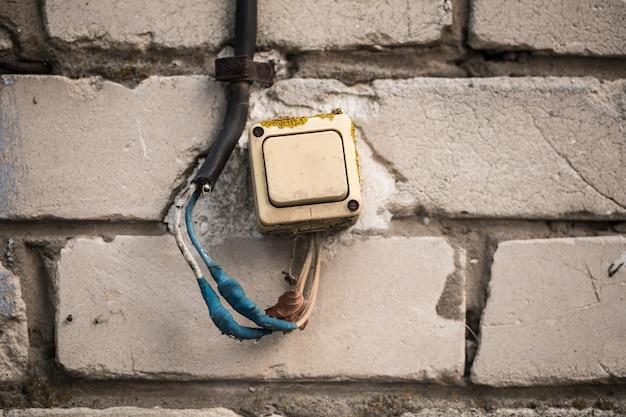 Stary włącznik na ceglanej ścianie skręcił niebieską taśmę.
