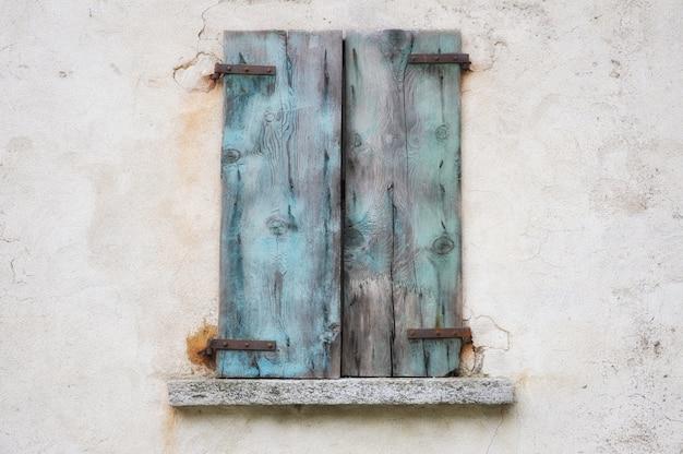Stary wyblakły mur z niebieskimi zardzewiałymi drewnianymi okiennicami