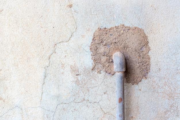 Stary, wyblakły stiuk ściany z fajki wodnej wystające z niego pęknięcia