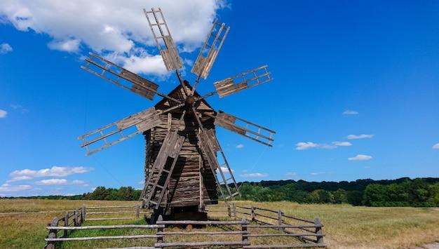 Stary zabytkowy drewniany wiatrak z połamanymi zniszczonymi żaglami ogrodzonymi w otwartym polu w słoneczny dzień błękitnego nieba