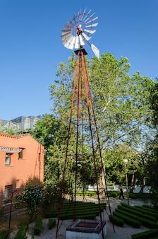 Stary zabytkowy wiatrak aermotor używany do pompowania wody i pięknego niebieskiego nieba