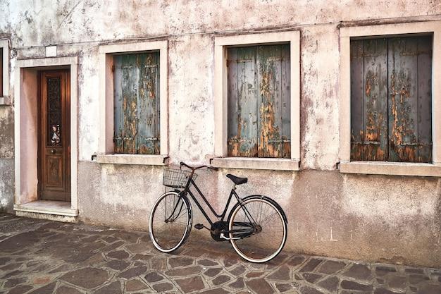 Stary zardzewiały rower pod starym murem na ulicy. włochy, wenecja, wyspa burano