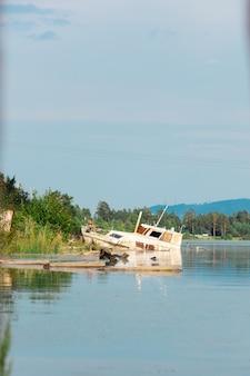 Stary zardzewiały statek na mieliźnie na brzegu zatoki rzeki. zanieczyszczenie ludzi odpadami przemysłowymi. widok pionowy