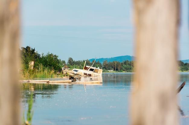 Stary zardzewiały statek na mieliźnie na brzegu zatoki rzeki. zanieczyszczenie ludzi odpadami przemysłowymi