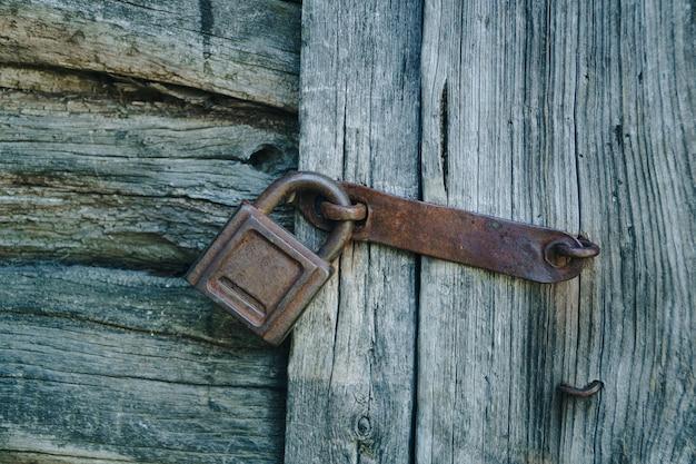 Stary zardzewiały zamek na stare drewniane drzwi