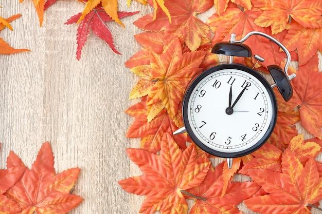 Stary zegar na jesień liściach na drewnianym stole na naturalnym tle