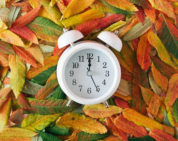 Stary zegar retro na jesiennym opadłym liściu. jesienny pomysł vintage.