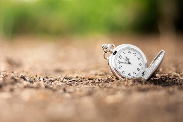 Stary zegarek kieszonkowy odrzuca się na ziemię. myślenie i kontrola pomysłów na czas.
