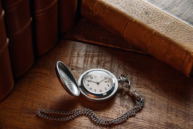 Stary zegarek kieszonkowy z łańcuszkiem leży na stole w pobliżu starych książek.