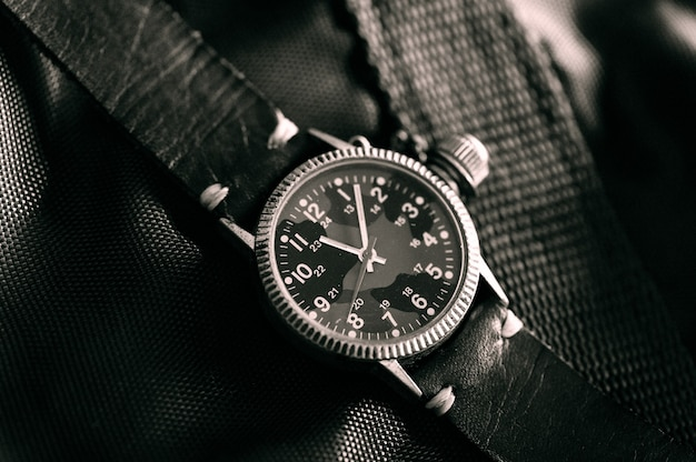 Stary zegarek na rękę w stylu wojskowym z tarczą w kamuflażu i skórzanym paskiem
