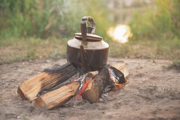 Stary żelazny czajnik stoi na płonącym drewnie, biwakuje