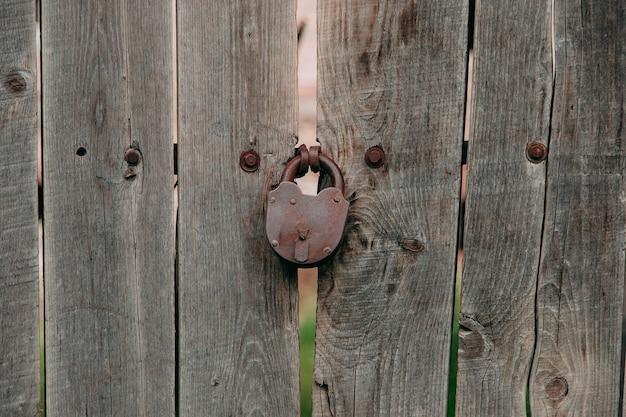 Stary żelazny zamek na drewnianej bramie, rustykalna stodoła.