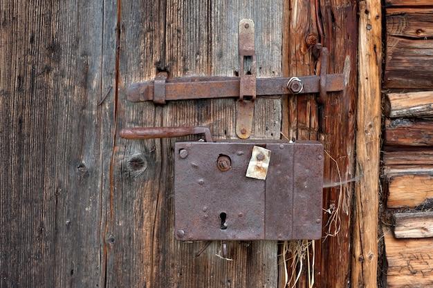 Stary żelazny zamek na drewnianych drzwiach stodoły