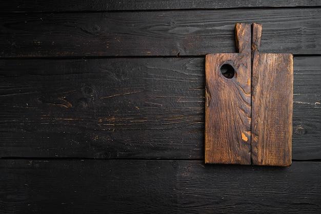 Stary zestaw desek do krojenia, płaski widok z góry, z kopią miejsca na tekst lub jedzenie, na czarnym tle drewnianego stołu
