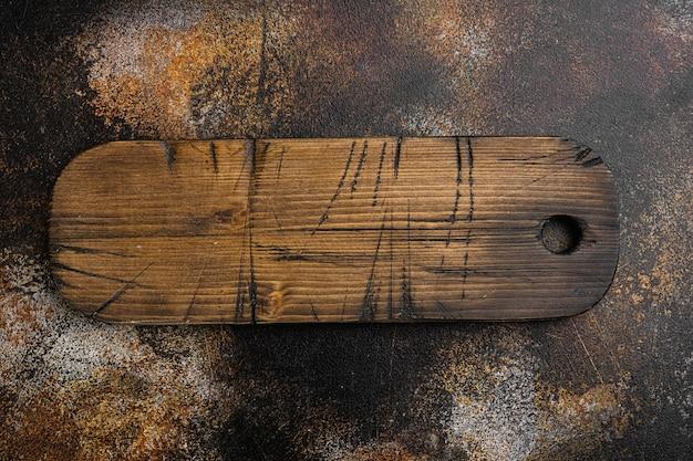 Stary zestaw desek do krojenia, płaski widok z góry, z kopią miejsca na tekst lub jedzenie, na starym ciemnym tle rustykalnym stołu