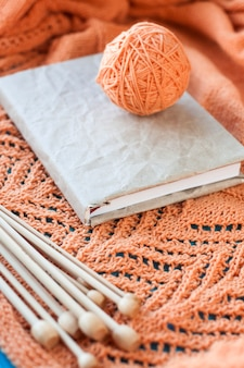 Stary zeszyt na płyty, kłębek przędzy i iglice leżące na drewnianej pomarańczowej dzianinie w kratę