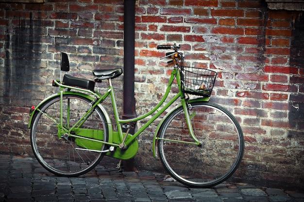 Stary zielony rower retro z koszem na ścianie grunge w rawennie we włoszech
