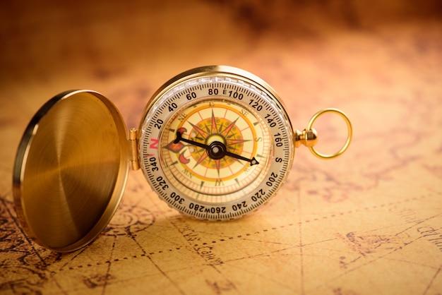 Stary złoty rocznika kompas na rocznik mapie