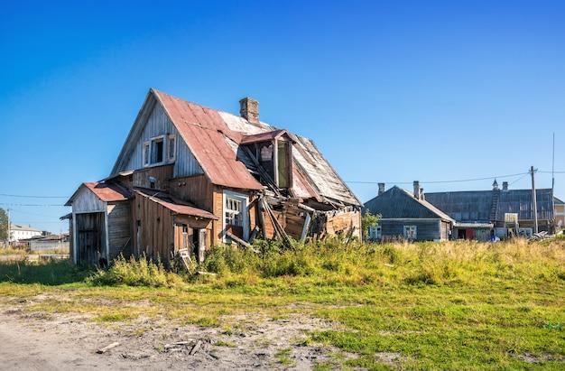 Stary zniszczony drewniany dom na wyspach sołowieckich pod błękitnym niebem jesienią