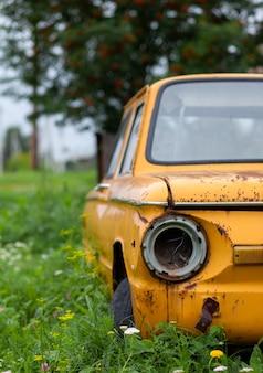 Stary żółty rozbity samochód w stylu vintage. opuszczony zardzewiały żółty samochód. zbliżenie reflektorów przedniego widoku zardzewiałego, zepsutego, porzuconego samochodu w pobliżu domu. pojęcie opuszczonego samochodu używanego.