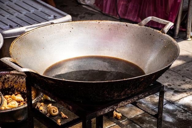 Stary zużyty olej kuchenny i wygląda jak czarno-brązowy kolor na brudnej żelaznej patelni. rakotwórczy w żywności, powodujący raka. koncepcja niezdrowego stylu życia.