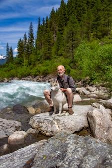 Starzec i pies zaprzęgowy chodzą w pobliżu rzeki. alpejski krajobraz. aktywny emeryt rekreacyjny. starszy mężczyzna się uśmiecha. spaceruj z siberian husky.