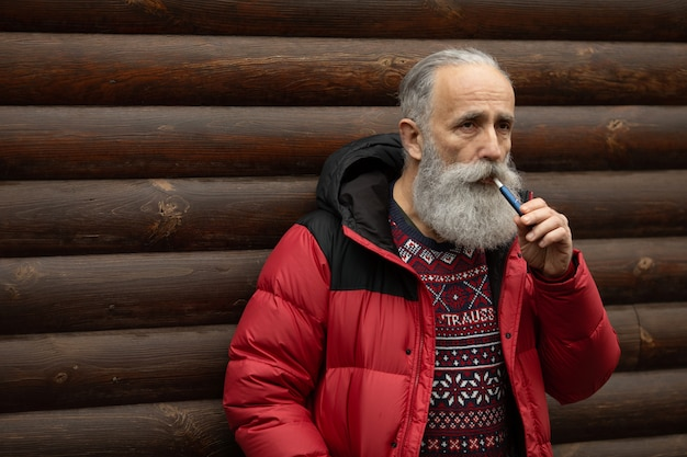 Starzec z brodą i wąsami w różowej koszulce pali.
