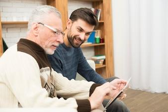 Starzejący się mężczyzna i młody pozytywny facet używa pastylkę na kozetce