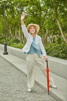 Starzejąca się biała ładna podróżująca kobieta w przypadkowym ubraniu stoi w pobliżu drogi i macha ręką i uśmiecha się.