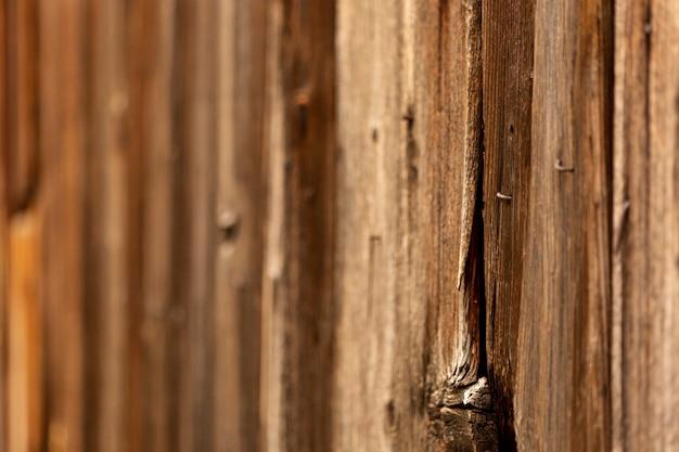 Starzejąca się drewniana powierzchnia z sękiem i zardzewiałymi gwoździami