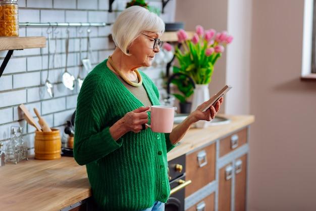 Starzejąca się elegancka dama ze smutkiem patrząca na ramkę w dłoniach trzymająca filiżankę kawy w kuchni
