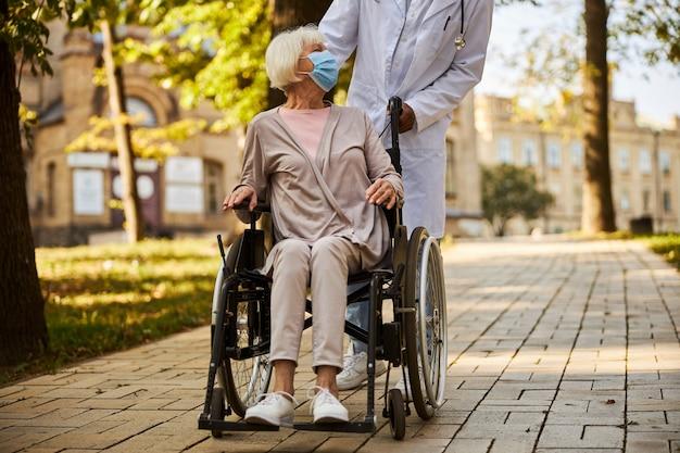 Starzejąca się kaukaska kobieta jedzie na wózku inwalidzkim z pomocą pracownika medycznego