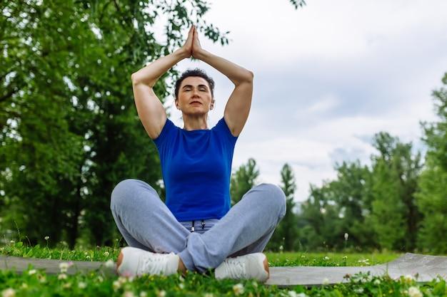 Starzejąca się kobieta robi joga ćwiczeniu w parku. starsza kobieta ćwiczy joga outdor