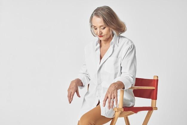 Starzejąca się kobieta w białej koszuli siedzi na krześle z czerwonymi ustami na białym tle